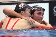 Yui Ohashi, of Japan, left, is embraced by Emma Weyant, of United States, after winning the final of the women's 400-meter Individual medley at the 2020 Summer Olympics, Sunday, July 25, 2021, in Tokyo, Japan. (AP Photo/Matthias Schrader)