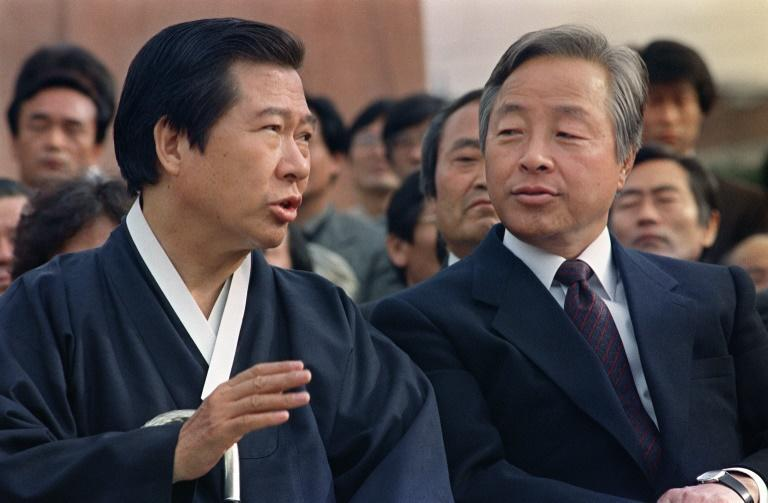 Then opposition presidential candidates Kim Dae-Jung (L) and Kim Young-Sam (R) chat during a rally held at the Korea University in Seoul on October 25, 1987