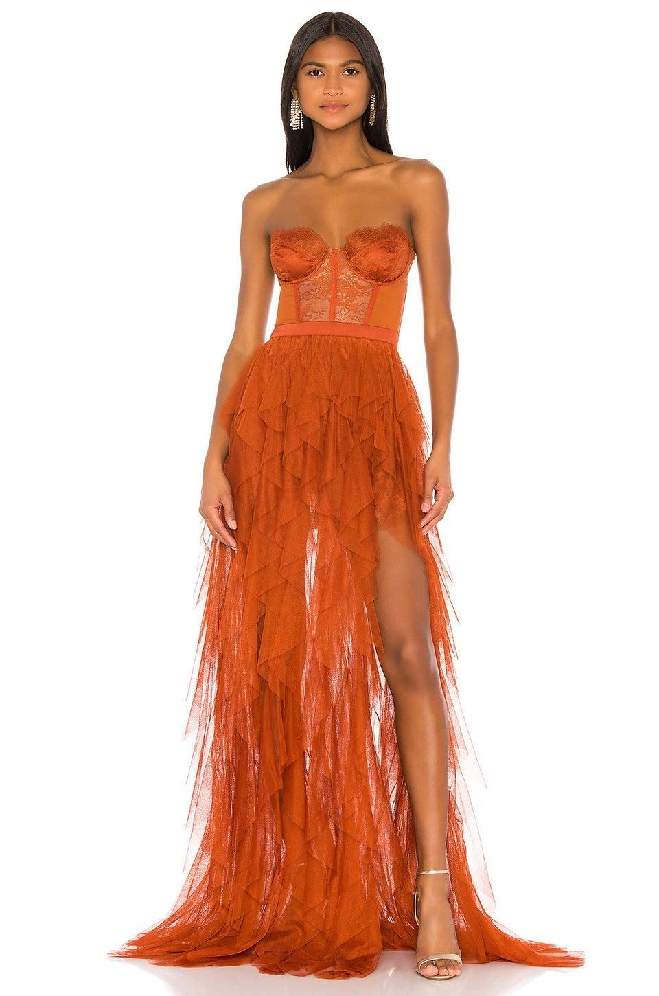 """<h2>For Love & Lemons Bustier Gown In Deep Orange</h2><br>This figure-hugging gown is sheer fun, offering a corset-like bodice structure paired with a chopped-up, leg-baring see-thru skirt. <br><br><em>Shop For Love & Lemons at <strong><a href=""""https://www.revolve.com/for-love-lemons/br/cec5a0"""" rel=""""nofollow noopener"""" target=""""_blank"""" data-ylk=""""slk:Revolve"""" class=""""link rapid-noclick-resp"""">Revolve</a></strong></em> <br><br><strong>For Love & Lemons</strong> Sienna Bustier Gown, $, available at <a href=""""https://go.skimresources.com/?id=30283X879131&url=https%3A%2F%2Fwww.revolve.com%2Ffor-love-lemons-x-revolve-bustier-gown%2Fdp%2FFORL-WD734%2F%3Fd%3DWomens"""" rel=""""nofollow noopener"""" target=""""_blank"""" data-ylk=""""slk:Revolve"""" class=""""link rapid-noclick-resp"""">Revolve</a>"""