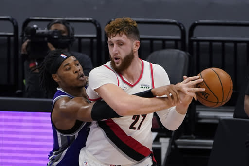 Sacramento Kings center Richaun Holmes, left, hits the ball out of the hands of Portland Trail Blazers center Jusuf Nurkic during the second half of an NBA basketball game in Sacramento, Calif., Wednesday, Jan. 13, 2021. The Trail Blazers won 132-126. (AP Photo/Rich Pedroncelli)