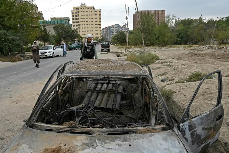 A Taliban fighter investigates a damaged car with what appears to be a damaged launcher in the back, after multiple rockets were fired in Kabul on August 30, 2021 (AFP/WAKIL KOHSAR)