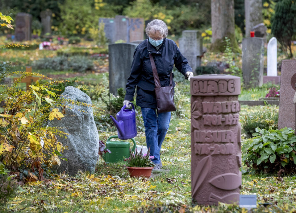 An elderly woman wearing a face mask takes care of a grave at the main cemetery in Frankfurt, Germany, Wednesday, Oct. 28, 2020. (AP Photo/Michael Probst)