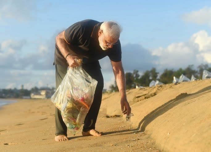 In this handout photo provided by the Indian Prime Minister's Office, Prime Minister Narendra Modi picks trash from a beach in Mamallapuram, India. As part of his cleanliness drive, Indian Prime Minister Narendra Modi has picked up trash from a beach in the southern temple town where he hosted Chinese President Xi Jinping. (Indian Prime Minister's Office via AP)