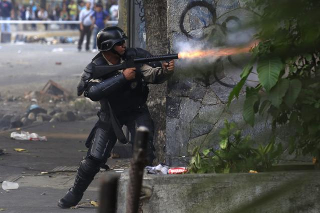 A national policeman fires tear gas at anti-government protesters hiding in an apartment building during a protest in Caracas March 8, 2014. Latin American foreign ministers will meet next week to discuss the unrest in Venezuela that has left at least 20 dead and convulsed the South American OPEC nation, diplomatic sources said on Friday. REUTERS/Tomas Bravo (VENEZUELA - Tags: POLITICS CIVIL UNREST)