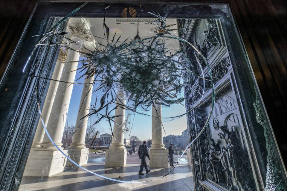"""FILE - In this Jan. 12, 2021, file photo shattered glass from the attack on Congress by a violent pro-Trump mob is seen in doors leading to the Capitol Rotunda in Washington. Violent extremists motivated by political grievances and racial biases pose an """"elevated threat"""" to the U.S. homeland, officials said Wednesday, March 17, in a unclassified intelligence report released more than two months after a violent mob of insurrectionists stormed the U.S. Capitol. (AP Photo/J. Scott Applewhite, File)"""