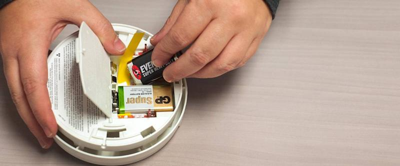 A man changes the battery in his smoke detector