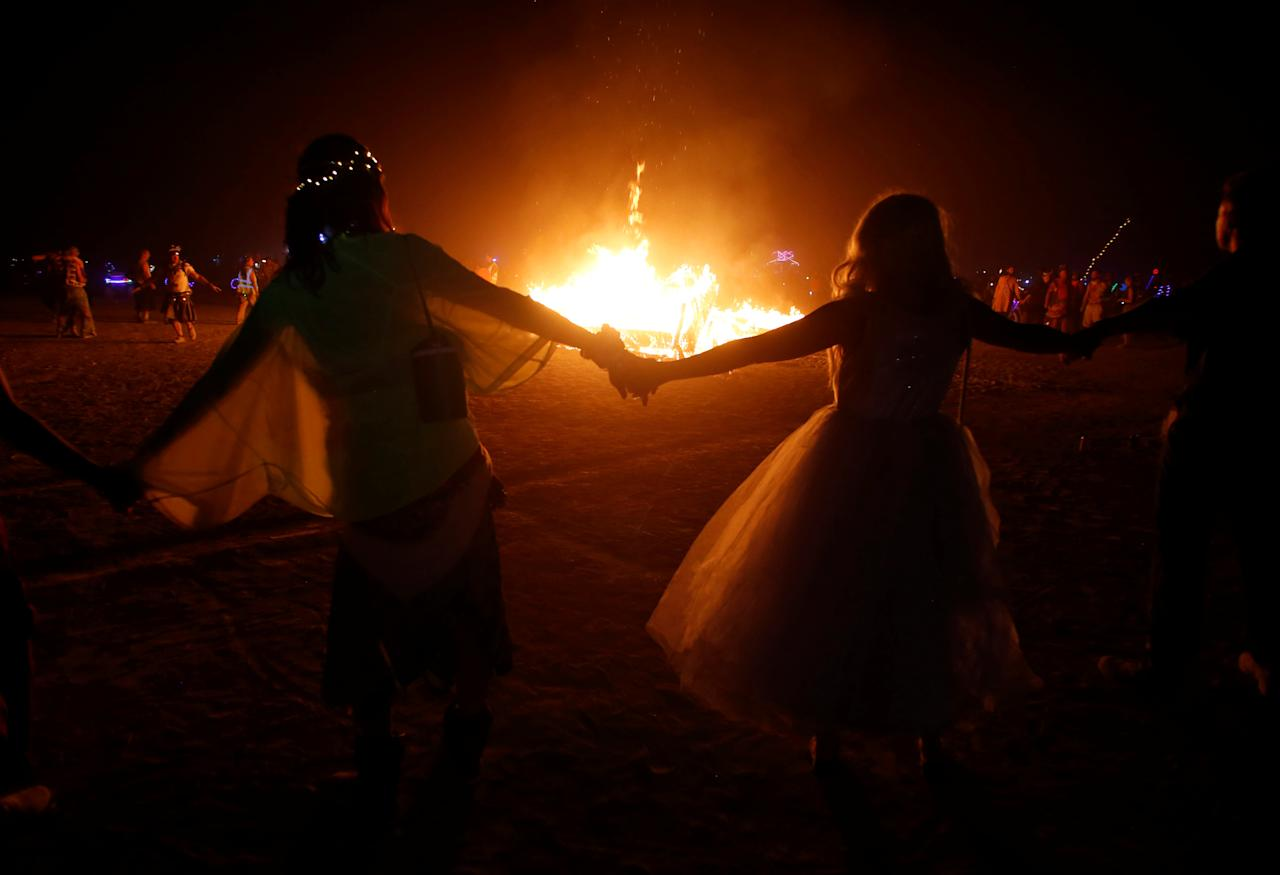 <p>Participants surround a burning art installation as approximately 70,000 people from all over the world gathered for the annual Burning Man arts and music festival in the Black Rock Desert of Nevada, Sept. 1, 2017. (Photo: Jim Urquhart/Reuters) </p>