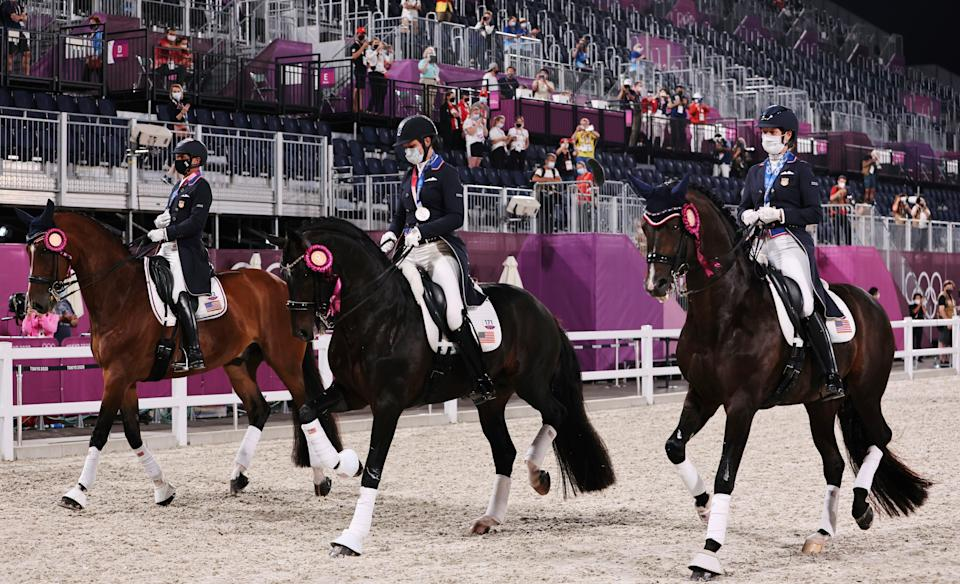 Silver medalists Adrienne Lyle, Steffen Peters and Sabine Schut-Kery of the United States ride together after the medal ceremony of the Equestrian Dressage team final.