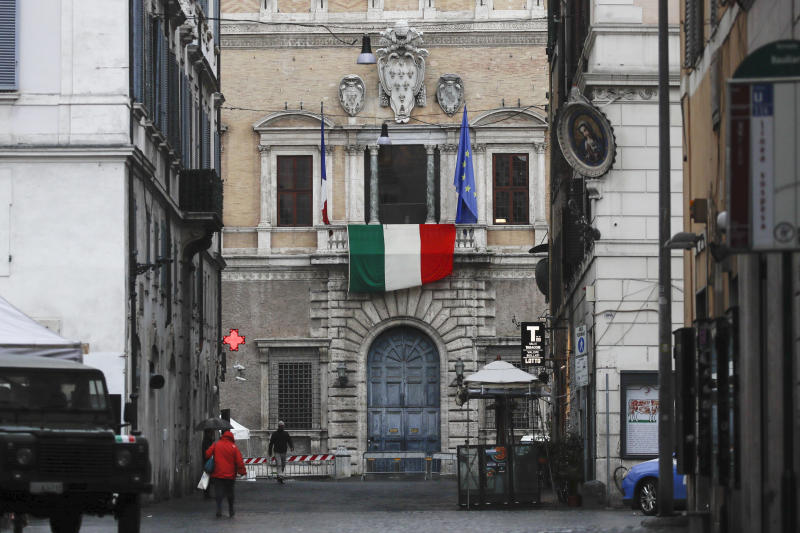The Italian flag hangs from the balcony of the French Embassy in Rome, Friday, March 27, 2020. As the coronavirus claims lives, ruins livelihoods and wreaks economic havoc, tensions are rising between European Union countries over how best to respond as the pandemic overwhelms some member nations, once more raising troubling questions about the EU's ability to stand united in times of crisis. The new coronavirus causes mild or moderate symptoms for most people, but for some, especially older adults and people with existing health problems, it can cause more severe illness or death. (AP Photo/Alessandra Tarantino)