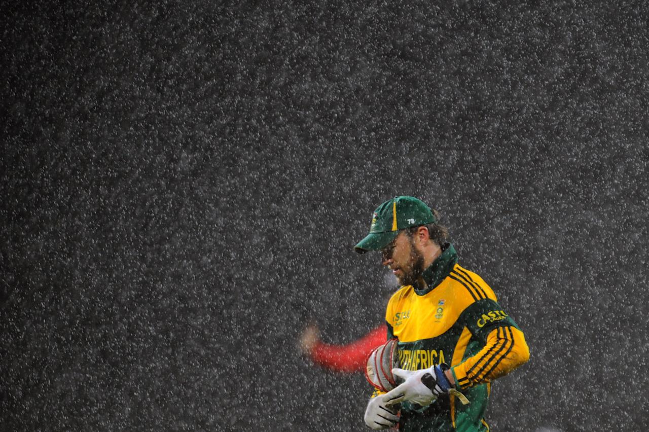 South African cricket captain AB de Villiers leaves the pitch after rain stopped play during second One Day International (ODI) match between Sri Lanka and South Africa at the R. Premadasa Stadium in Colombo on July 23, 2013. AFP PHOTO/Ishara S. KODIKARA        (Photo credit should read Ishara S.KODIKARA/AFP/Getty Images)