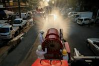 Firefighters spray disinfectant along a street in Yangon