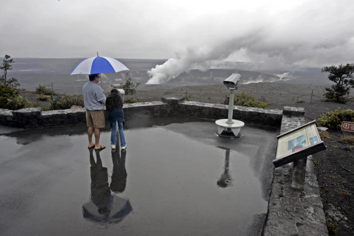 FILE - In this file photo from Sunday, March 8, 2009, Greg Rapozo and his daughter Kaydee, of Hilo, Hawaii take a rainy-day look at a plume of steam and gas emitting from the year-old fumarole in the Halemaumau Crater of Kilauea's summit caldera in Hawaii Volcanoes National Park. Part of what makes living in Hawaii so pleasant is the gentle breezes. Nowadays, these breezes, called trade winds, are declining, a drop that's slowly changing life across the islands. (AP Photo/Chris Stewart)