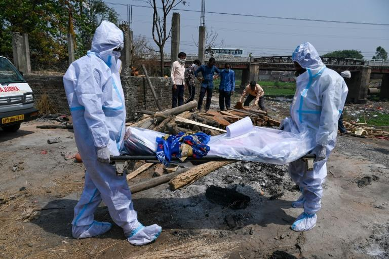 Relatives wearing a personal protective equipment (PPE) suit carry the dead body of a Covid-19 victim at the crematorium in Moradabad