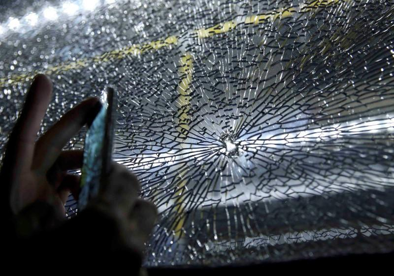 Journalists look at the window of a bus reportedly hit by bullets. (Reuters)