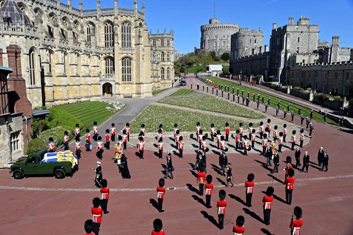 Prince Philip's coffin is at the front of a procession while military members in red coats and bearskin hats stand nearby.