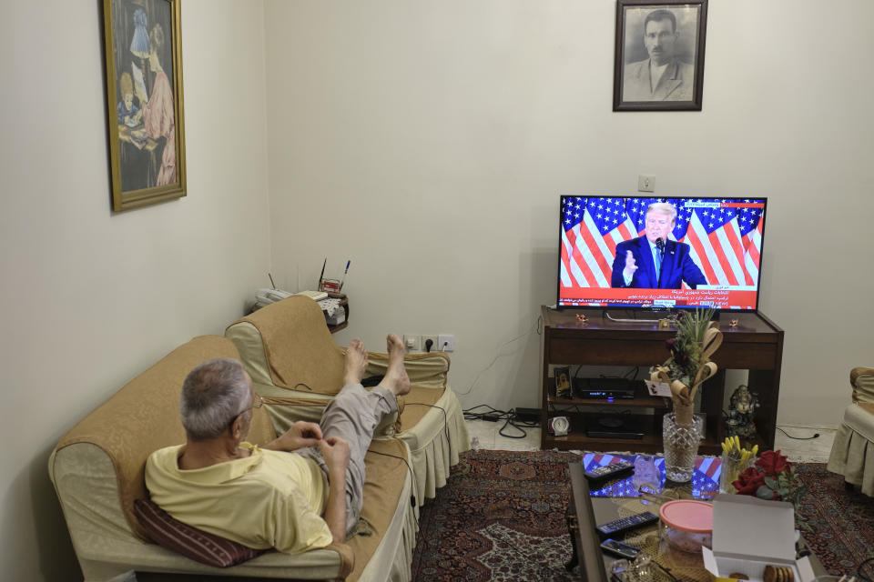 An Iranian man watches television as the US President Donald Trump addresses a crowd.