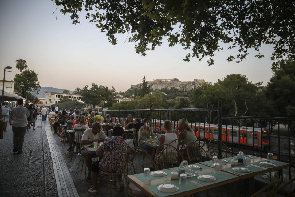 People sit at a restaurant in the Plaka district of Athens, with the ancient Acropolis in the background on Friday July 16, 2021. Greece became the latest on Friday, with a new measure coming into effect requiring proof of vaccination or recent recovery from COVID-19 for access to indoor restaurants, cafes, bars and movie theaters. Children can enter with negative tests. (AP Photo/Petros Giannakouris)