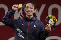 Kuo Hsing-Chun of Taiwan celebrates on the podium after winning the gold medal in the women's 59kg weightlifting event, at the 2020 Summer Olympics, Tuesday, July 27, 2021, in Tokyo, Japan. She won gold medal and sets a new Olympic record. (AP Photo/Luca Bruno)