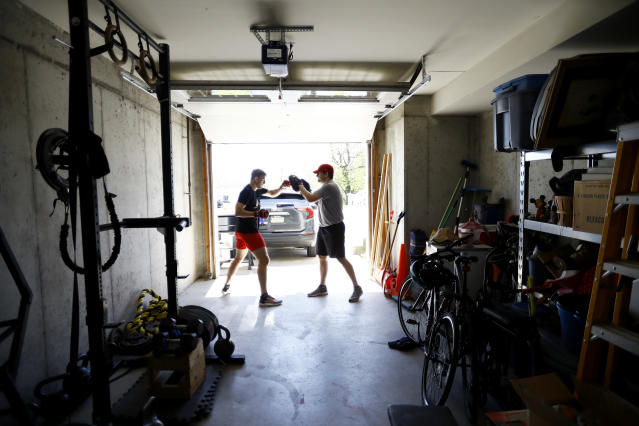 Fighter Kyle Daukaus, left, trains with his brother Chris Daukaus in their garage, Saturday, May 2, 2020, in Philadelphia. Kyle, a rising star in the regional MMA promotion Cage Fury Fighting Championships, is still chasing his dream of getting the call to fight for UFC despite the coronavirus pandemic. (AP Photo/Matt Slocum)