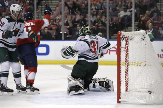 Florida Panthers center Jonathan Huberdeau (11) reacts after the puck gets past Minnesota Wild goaltender Kaapo Kahkonen (31) on a goal scored by Florida Panthers center Aleksander Barkov, not shown, during the first period of an NHL hockey game, Tuesday, Dec. 3, 2019, in Sunrise, Fla. (AP Photo/Lynne Sladky)