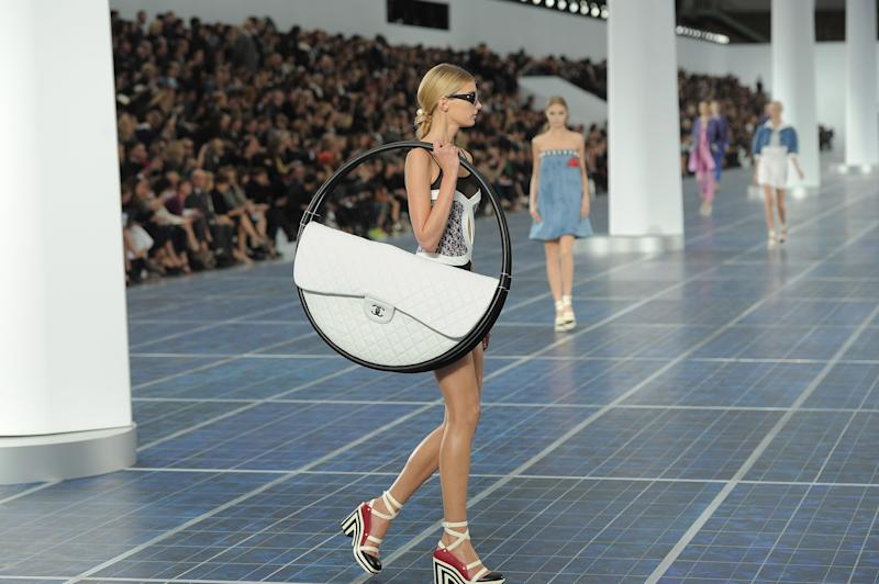 "Of all of Lagerfeld's reinterpretations of the classic quilted Chanel leather bag, the most, um, singular was the hula hoop version that appeared during Chanel's show for spring/summer 2013, which promptly became the talk of the season. The bag, Lagerfeld later explained, ""is for the beach! You need space for the beach towel. Then you can put it into the sand and hang things on it."""
