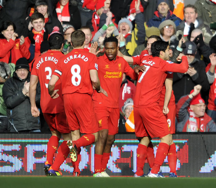 Liverpool's Luis Suarez right, celebrates with his team-mates after he scored the first goal of the game for his side during their English Premier League soccer match against Tottenham Hotspur at Anfield in Liverpool, England, Sunday March 10, 2013. (AP Photo/Clint Hughes)