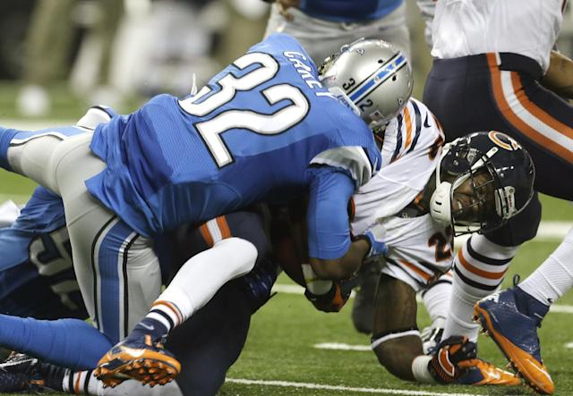 Chicago Bears running back Matt Forte (22) is stopped by Detroit Lions strong safety Don Carey (32) during the first quarter of an NFL football game at Ford Field in Detroit, Sunday, Sept. 29, 2013. (AP Photo/Carlos Osorio)