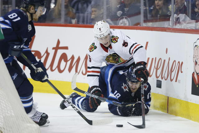 Winnipeg Jets left wing Kyle Connor (81) picks up the loose puck as center Bryan Little (18) and Chicago Blackhawks defenceman Connor Murphy (5) fight for it in Chicago territory during the second period of an NHL hockey game Thursday, March 15, 2018, in Winnipeg, Manitoba. (John Woods/The Canadian Press via AP)