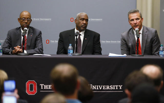 Ohio State football coach Urban Meyer, right, answers questions as athletic director Gene Smith and university President Michael Drake, left, listen during a news conference in Columbus, Ohio, Wednesday, Aug. 22, 2018. Ohio State suspended Meyer on Wednesday for three games for mishandling domestic violence accusations, punishing one of the sport's most prominent leaders for keeping an assistant on staff for several years after the coach's wife accused him of abuse. Gene Smith was suspended from Aug. 31 through Sept. 16. (AP Photo/Paul Vernon)