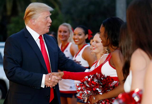 U.S. President Donald Trump greets cheerleaders with the Florida Atlantic University Marching Band before hosting a Super Bowl LII watch party at Trump International Golf Club in Palm Beach, Florida U.S., February 4, 2018. REUTERS/Leah Millis
