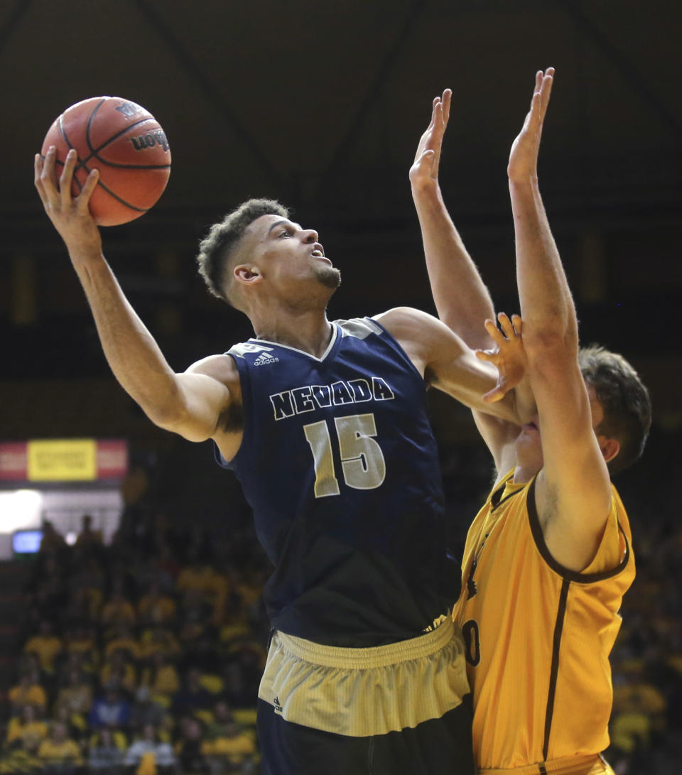 Nevada forward Trey Porter (15) shoots over Wyoming forward Hunter Thompson during the first half of an NCAA college basketball game Saturday, Feb. 16, 2019, in Laramie, Wyo. (AP Photo/Jacob Byk)