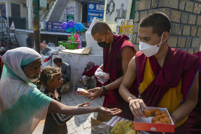 Exile Tibetan Buddhist monks distribute sweets and packets of juice to the public to celebrate the 86th birthday of their spiritual leader the Dalai Lama, outside the gate of their monastery in Dharmsala, India, Tuesday, July 6, 2021. (AP Photo/Ashwini Bhatia)