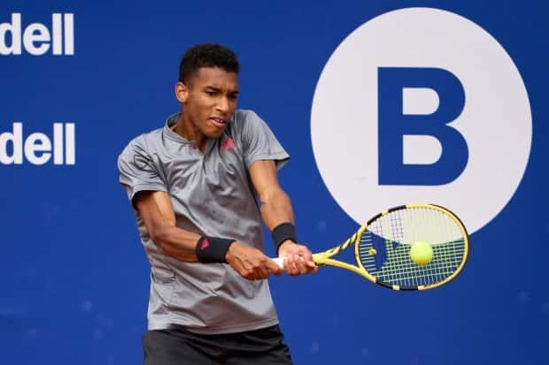 Canada's Felix Auger-Aliassime plays a backhand against fellow Canadian Denis Shapovalov in their third round match at the Barcelona Open Banc Sabadell 2021 in Barcelona on Thursday. (Alex Caparros/Getty Images - image credit)