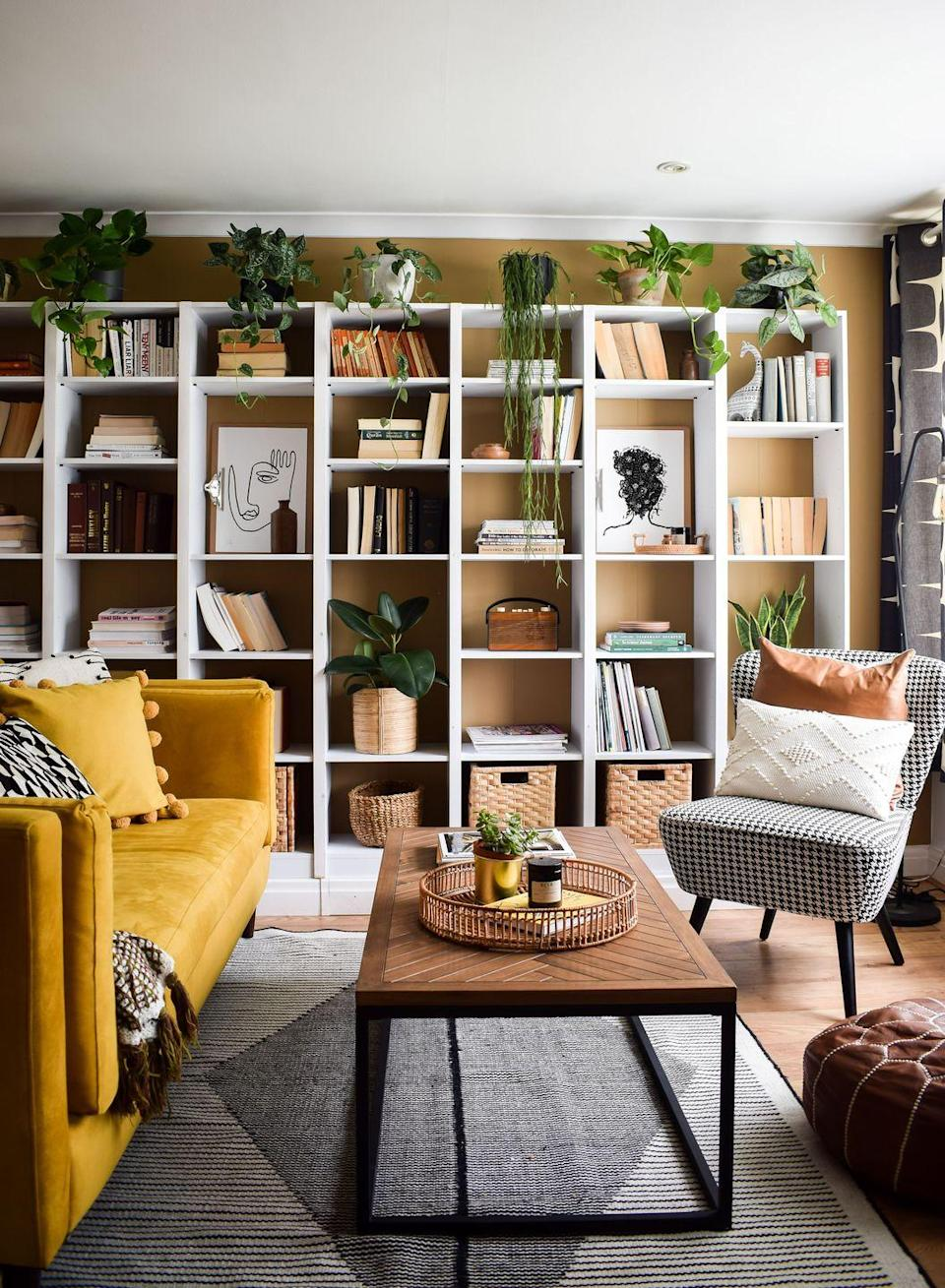 """<p>""""This wall-to-wall shelving system in our living room are renter-friendly and are actually built on a custom platform. I love books and this is a great way to store them. The lower baskets on the shelves are for toy storage. The mustard yellow sofa is probably my favourite thing in this room – it honestly makes such a huge statement.""""</p>"""