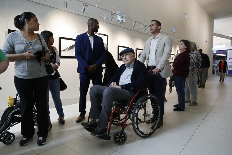 Former U.S. Sen. Harry Reid, center, waits in line to vote at an early voting site at the East Las Vegas library, Saturday, Feb. 15, 2020, in Las Vegas. (AP Photo/John Locher)