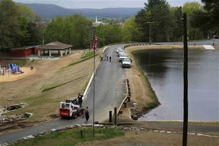 Workers put the finishing touches on the earthen dam at Robinhood Park Reservoir in Keene, New Hampshire May 16, 2014. Residents of this city of 23,000 people have faced repeated flooding in recent years including three floods considered 100-year events in the past decade alone. REUTERS/Brian Snyder