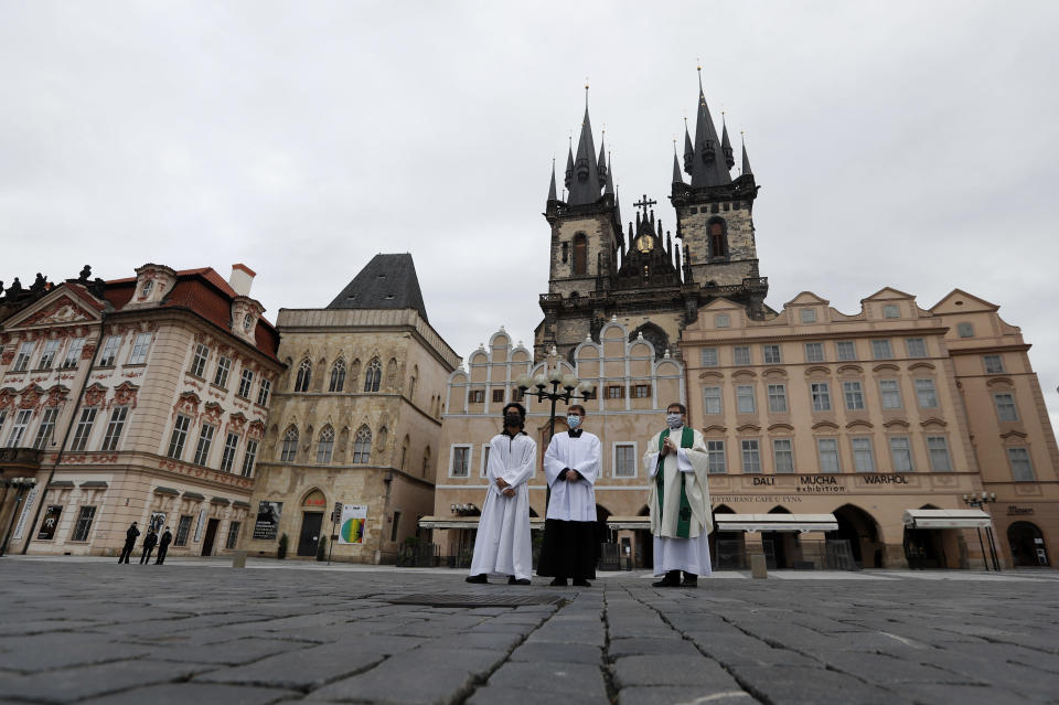 Priest Jiri Korda, right, arrives to celebrate an outdoor mass at Old Town Square in Prague, Czech Republic, Sunday, Oct. 18, 2020. As Czech Republic battles new spike of coronavirus infections newly adopted COVID-19 restrictive measures limit indoor gatherings to six people or less. (AP Photo/Petr David Josek)