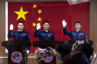 Chinese astronauts, from left, Tang Hongbo, Nie Haisheng, and Liu Boming wave at a press conference at the Jiuquan Satellite Launch Center ahead of the Shenzhou-12 launch from Jiuquan in northwestern China, Wednesday, June 16, 2021. China plans on Thursday to launch three astronauts onboard the Shenzhou-12 spaceship, who will be the first crew members to live on China's new orbiting space station Tianhe, or Heavenly Harmony from the Jiuquan Satellite Launch Center in northwest China. (AP Photo/Ng Han Guan)