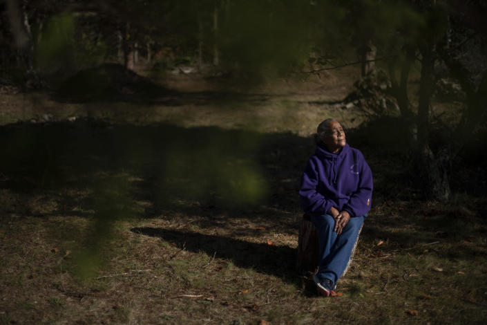 """Hazel Harding Currence, 78, a Herring Pond Wampanoag Tribe Elder, sits for a portrait in her backyard in Bourne, Mass., Tuesday, Oct. 6, 2020. """"We were exposed to disease. We were exposed to slavery. I mean, what happened here was people who came not just for religion, that might have been their purpose of leaving their homeland, but they came here and wanted to wipe out the existence of a whole culture,"""" said Currence. """"We should have never been treated the way that we were, our ancestors,"""" Currence added. """"I think that if they were here now, if they were looking down on us, I think they'd be very proud at the movement that's going forward now."""" (AP Photo/David Goldman)"""
