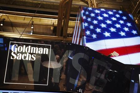 The Goldman Sachs logo is displayed on a post above the floor of the New York Stock Exchange
