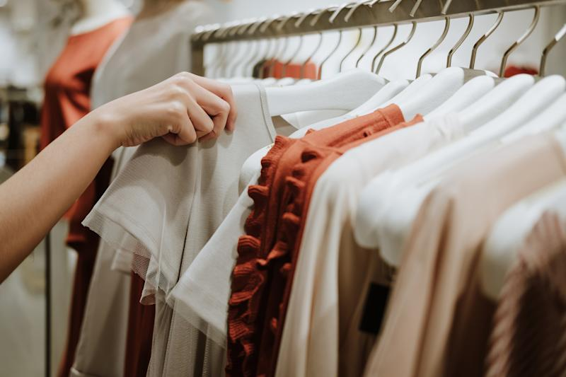 A woman inspecting clothes on a retailer rack.