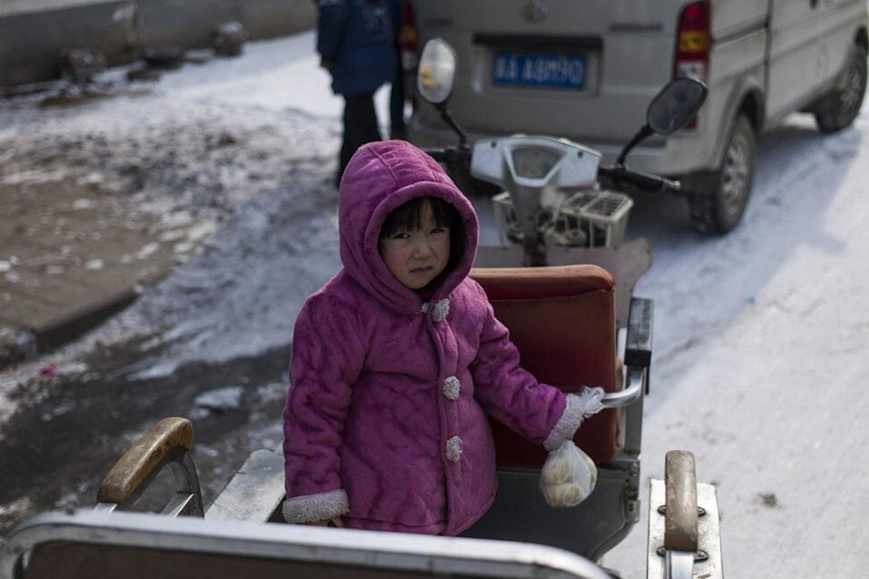 A girl wearing a jacket to keep warm sits on a vehicle at Tuntou village, on the outskirts of Shijiazhuang, Hebei province. Photo: AFP