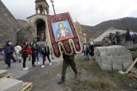 A church worker carry gonfalons out from the 12th-13th century Orthodox Dadivank Monastery on the outskirts of Kalbajar, the separatist region of Nagorno-Karabakh, on Friday, Nov. 13, 2020. Under an agreement ending weeks of intense fighting over Nagorno-Karabakh, some Armenian-held territories, such as this area, will pass to Azerbaijan. (AP Photo/Sergei Grits)