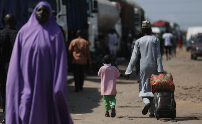 A man pulls a suitcase and walks with his son as people protest along the Kaduna-Abuja highway in Gauruka, near Abuja, Nigeria - Monday 24 May 2021