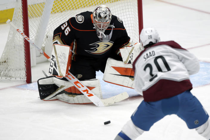 Anaheim Ducks goaltender John Gibson, left, makes a stop on a shot by Colorado Avalanche left wing Brandon Saad during the third period of an NHL hockey game in Anaheim, Calif., Sunday, Jan. 24, 2021. (AP Photo/Alex Gallardo)