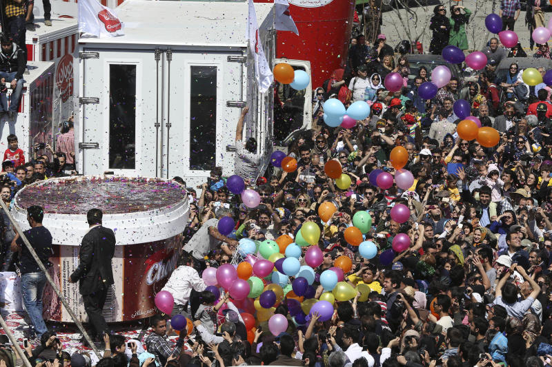 5-tons of ice-cream, left, made by Iranian Choopan dairy is displayed during a ceremony at the Tochal mountainous area of northern Tehran, Iran, Monday, April 1, 2013. Choopan dairy unveiled a 5-tons chocolate icecream, the largest in the world, according to the factory officials. (AP Photo/Ebrahim Noroozi)