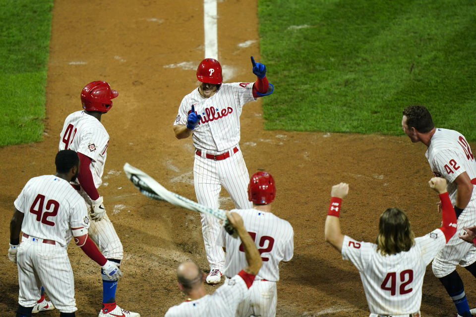 Philadelphia Phillies' Scott Kingery celebrates with teammates after hitting a game-winning three-run home run off Atlanta Braves pitcher Mark Melancon during the 11th inning of a baseball game, Friday, Aug. 28, 2020, in Philadelphia. (AP Photo/Matt Slocum)