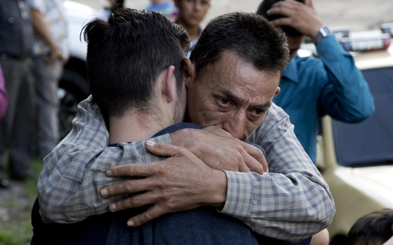 In this Oct. 9, 2019 photo, a father hugs his son outside the Migrant Assistance Office in San Salvador, El Salvador. Buses with deported Salvadorans, such as the son, arrive every day from the U.S. and Mexico. (AP Photo/Eduardo Verdugo)