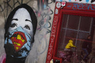 """A mother and her child are reflected as they pass a mural by artist FAKE, titled """"Super Nurse"""", paying tribute to all healthcare and medical professionals in times of the coronavirus, in Amsterdam, Netherlands, Sunday, April 19, 2020. (AP Photo/Peter Dejong)"""