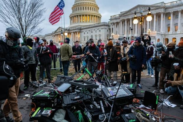 Media stand around some equipment damaged by pro-Trump protesters during the Jan. 6 riot at U.S. Capitol. Journalists and media critics interviewed for a recent CBC documentary, Big News, say that the media's catering to a polarized populace and widespread distrust in mainstream media is part of what led to the riot, which left five people, including a police officer dead. (Michael Nigro/Pacific Press/LightRocket/Getty Images - image credit)